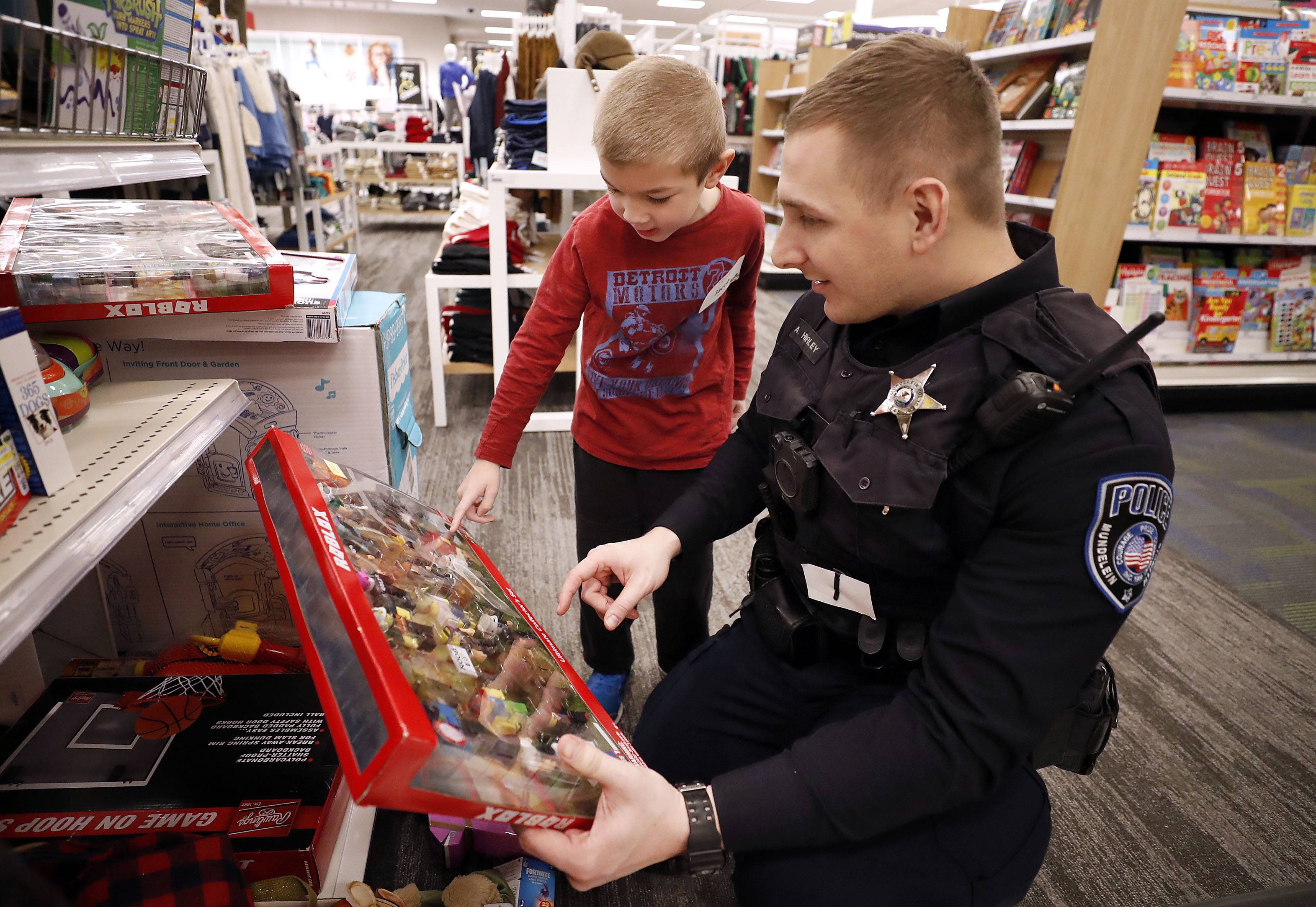 "Mundelein officer Austin Hurley helps 5-year-old Jacob Kapsalis pick out at toy during the annual ""Shop with a Cop"" program Saturday at the local Super Target."