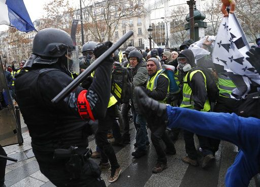 Police officers clash with demonstrators wearing yellow vests in Paris, Saturday, Dec. 8, 2018. Prized Paris monuments and normally bustling shopping meccas locked down Saturday and tens of thousands of police took position around France, fearing worsening violence in a new round of anti-government protests.