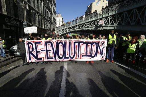 Demonstrators wearing yellow vests hold a banner during a march Saturday, Dec. 8, 2018 in Marseille, southern France. The grassroots movement began as resistance against a rise in taxes for diesel and gasoline, but quickly expanded to encompass frustration at stagnant incomes and the growing cost of living.