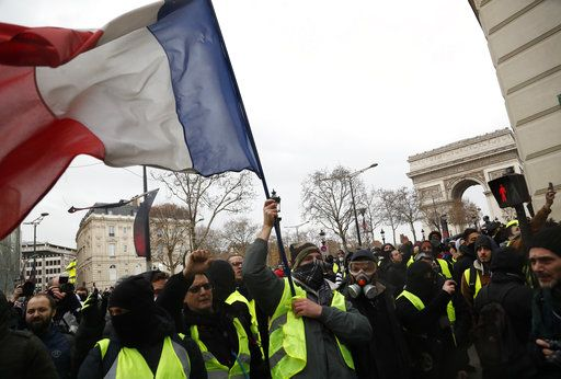"Demonstrators wearing yellow vests march down the Champs Elysees holding the French tricolor in Paris, Saturday, Dec. 8, 2018. Prized Paris monuments and normally bustling shopping meccas locked down and tens of thousands of police took position around France. Macron's government warned that Saturday's ""yellow vest"" protests in Paris will be hijacked by ""radicalized and rebellious"" crowds and become the most dangerous yet after three weeks of demonstrations."
