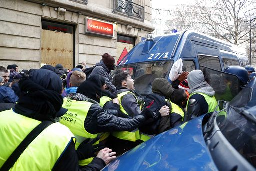 Police officers block demonstrators wearing yellow vests from entering a street in Paris, Saturday, Dec. 8, 2018. Prized Paris monuments and normally bustling shopping meccas locked down Saturday and tens of thousands of police took position around France, fearing worsening violence in a new round of anti-government protests.