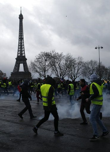 Demonstrators walk through tear gas during clashes Saturday, Dec. 8, 2018 in Paris. Crowds of yellow-vested protesters angry at President Emmanuel Macron and France's high taxes tried to converge on the presidential palace Saturday, some scuffling with police firing tear gas, amid exceptional security measures aimed at preventing a repeat of last week's rioting.