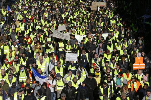 Demonstrators wearing yellow vests march Saturday, Dec. 8, 2018 in Marseille, southern France. The grassroots movement began as resistance against a rise in taxes for diesel and gasoline, but quickly expanded to encompass frustration at stagnant incomes and the growing cost of living.