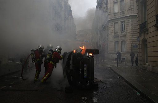 Firefighters try to extinguish a burning car after clashes Saturday, Dec. 8, 2018 in Paris. Crowds of yellow-vested protesters angry at President Emmanuel Macron and France's high taxes tried to converge on the presidential palace Saturday, some scuffling with police firing tear gas, amid exceptional security measures aimed at preventing a repeat of last week's rioting.