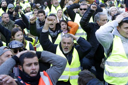 Demonstrators wearing yellow vests shout during a march Saturday, Dec. 8, 2018 in Marseille, southern France. The grassroots movement began as resistance against a rise in taxes for diesel and gasoline, but quickly expanded to encompass frustration at stagnant incomes and the growing cost of living.