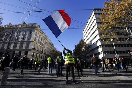 A demonstrator wearing a yellow vest waves the French flag during a march Saturday, Dec. 8, 2018 in Marseille, southern France. The grassroots movement began as resistance against a rise in taxes for diesel and gasoline, but quickly expanded to encompass frustration at stagnant incomes and the growing cost of living.