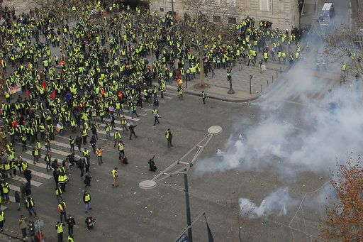 Riot police fire tear gas canisters at yellow-vested protesters gathered on the Paris' famed Champs-Elysees Avenue, France, Saturday, Dec. 8, 2018. Crowds of yellow-vested protesters angry at President Emmanuel Macron and France's high taxes tried to converge on the presidential palace Saturday, some scuffling with police firing tear gas, amid exceptional security measures aimed at preventing a repeat of last week's rioting.