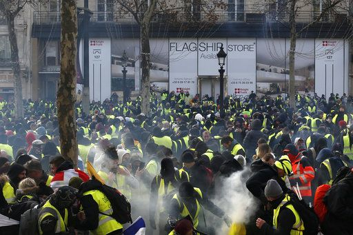 Demonstrators wearing yellow vests gather on the Champs-Elysees avenue Saturday, Dec. 8, 2018 in Paris. Crowds of yellow-vested protesters angry at President Emmanuel Macron and France's high taxes tried to converge on the presidential palace Saturday, some scuffling with police firing tear gas, amid exceptional security measures aimed at preventing a repeat of last week's rioting.