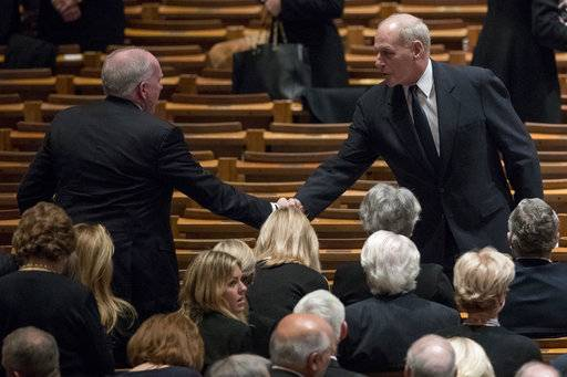 Former CIA Director John Brennan, left, shakes hands with President Donald Trump's Chief of Staff John Kelly, right, before a State Funeral for former President George H.W. Bush at the National Cathedral, Wednesday, Dec. 5, 2018, in Washington.