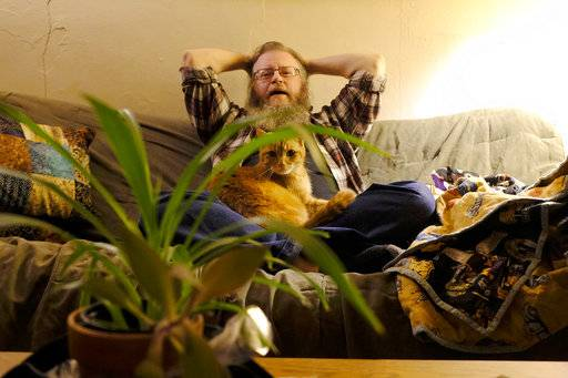 In this Nov. 19, 2018 photo,Dylan Caracker sits on his couch with an adopted cat at his home in Carbondale, Ill. Caracker said it took him decades to come to the realization that he identified as a man and that he should transition his gender. A transgender person has a different gender identity than what is assigned by the appearance of their genitals at birth. The way trans people express this varies.(Isaac Smith/The Southern, via AP)
