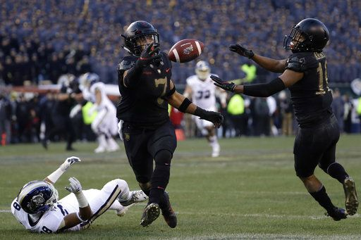 Army's Jaylon McClinton, center, intercepts a pass tipped by teammate Mike Reynolds, right, that was intended for Navy's Mychal Cooper during the first half of an NCAA college football game, Saturday, Dec. 8, 2018, in Philadelphia.