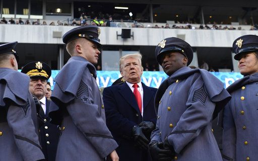 President Donald Trump, center, talks with Army Chief of Staff Gen. Mark Milley, left, watch from the stands before the Army-Navy NCAA college football game in Philadelphia, Saturday, Dec. 8, 2018.