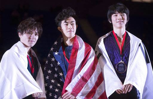 Nathan Chen, of the United States, center, celebrates his gold medal with silver medalist Shoma Uno, of Japan, left, and bronze medalist Jun-hwan Cha, of South Korea, right, following the men's free skate at the figure skating's Grand Prix Final in Vancouver, Friday, Dec. 7, 2018. (Jonathan Hayward/The Canadian Press via AP)