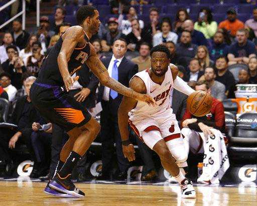 Miami Heat guard Dwyane Wade (3) drives around Phoenix Suns forward Trevor Ariza during the first half of an NBA basketball game Friday, Dec. 7, 2018, in Phoenix.