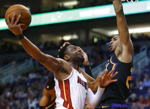Miami Heat guard Dwyane Wade shoots in front of Phoenix Suns forward Mikal Bridges (25) during the first half of an NBA basketball game Friday, Dec. 7, 2018, in Phoenix.