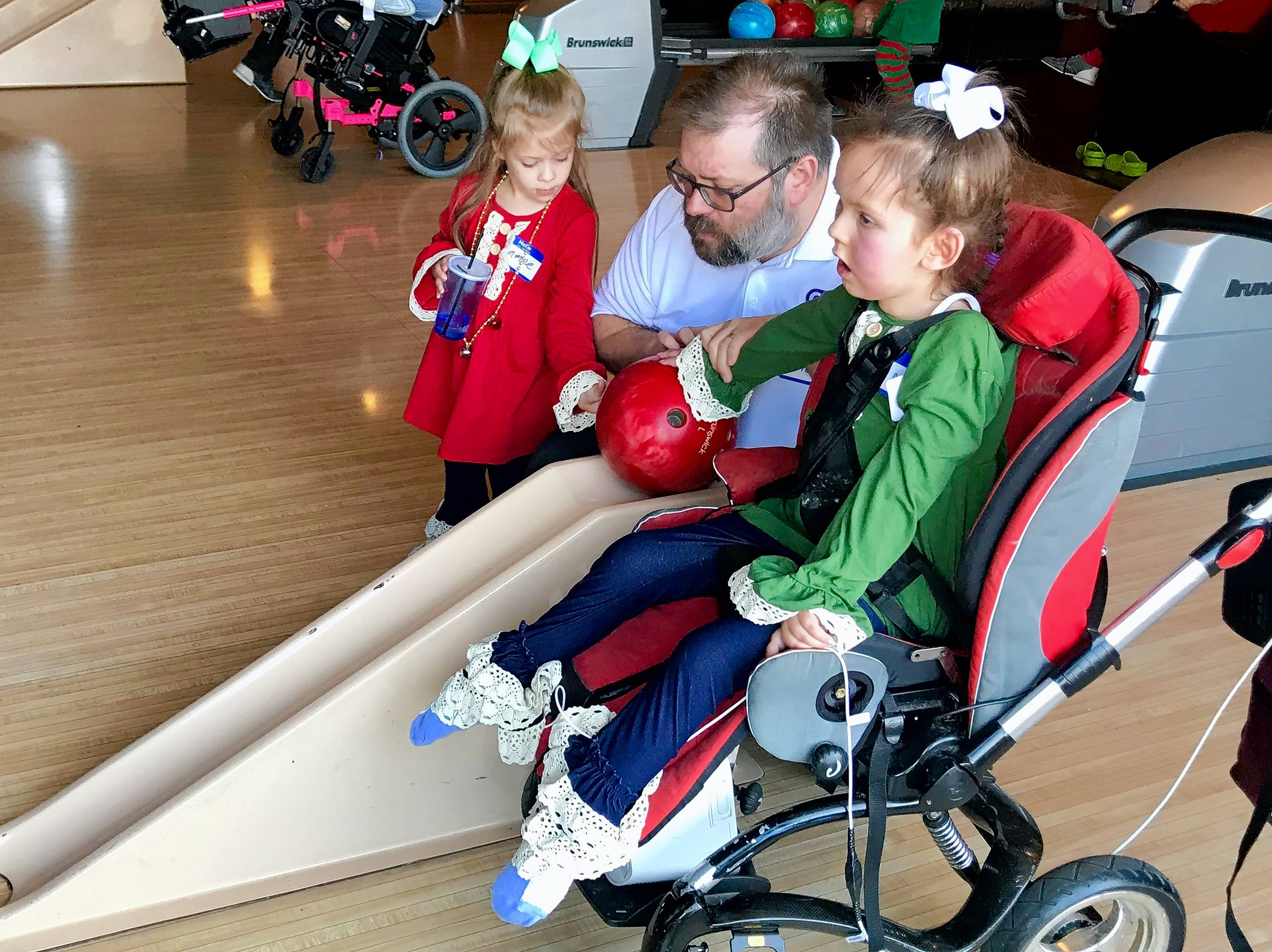 Mckenna Jurgovan, 7, of South Elgin, right, bowls Sunday with help from her dad, Eric, and 4-year-old sister, Emery, during a JourneyCare event at Pinstripes in Oak Brook.