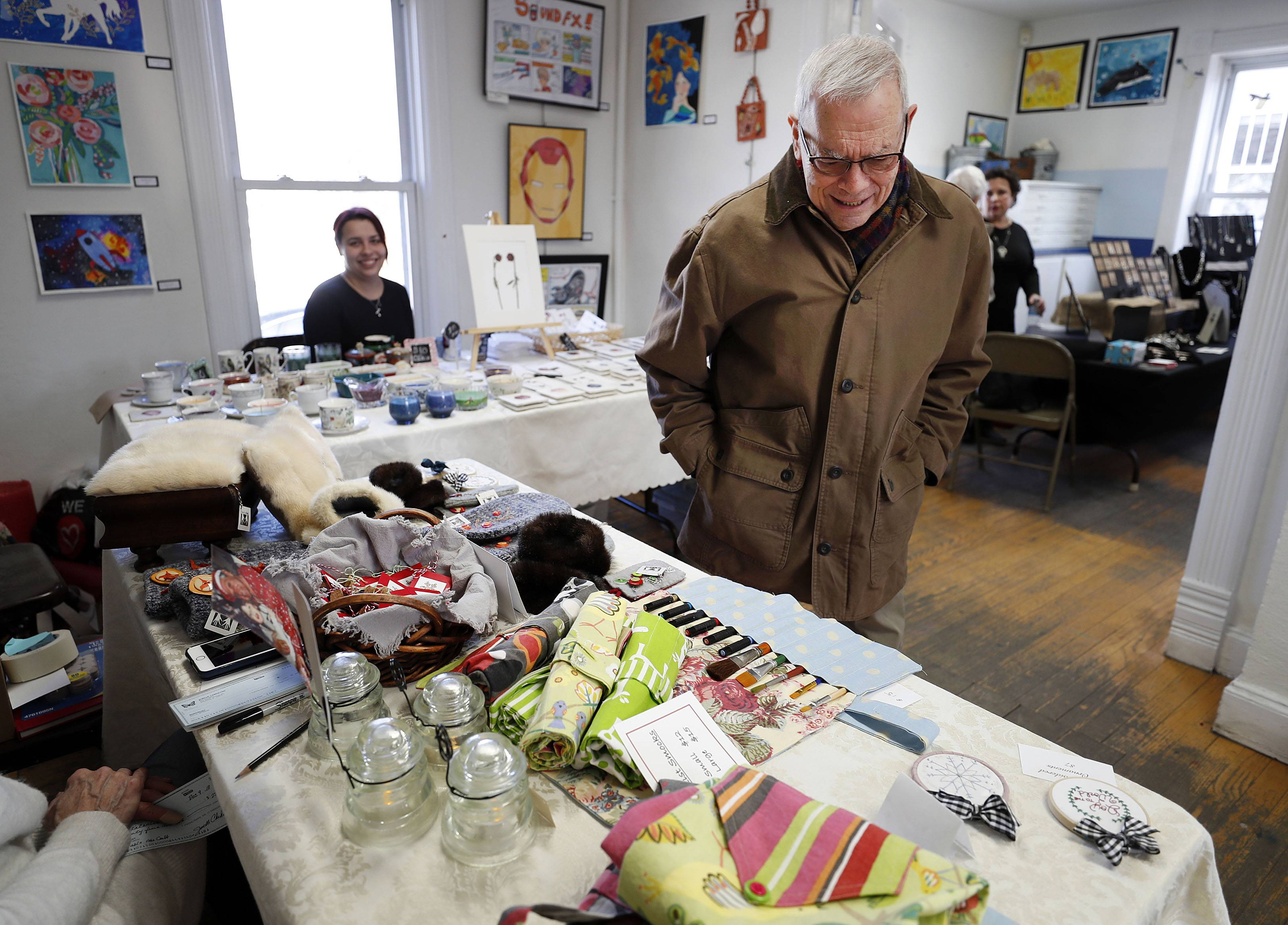D. Larry Friedman of Buffalo Grove looks over some of the work on display Sunday during an arts and crafts fair at Kaleidoscope School of Fine Art in Barrington.