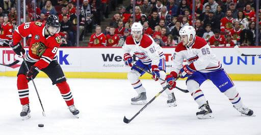Chicago Blackhawks right wing Patrick Kane (88) is defended by Montreal Canadiens right wing Andrew Shaw (65) and center Jonathan Drouin (92) during the second period of an NHL hockey game Sunday, Dec. 9, 2018, in Chicago.