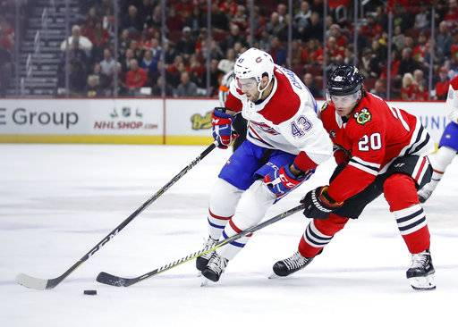Montreal Canadiens center Michael Chaput (43) battles for the puck with Chicago Blackhawks left wing Brandon Saad (20) during the first period of an NHL hockey game Sunday, Dec. 9, 2018, in Chicago.