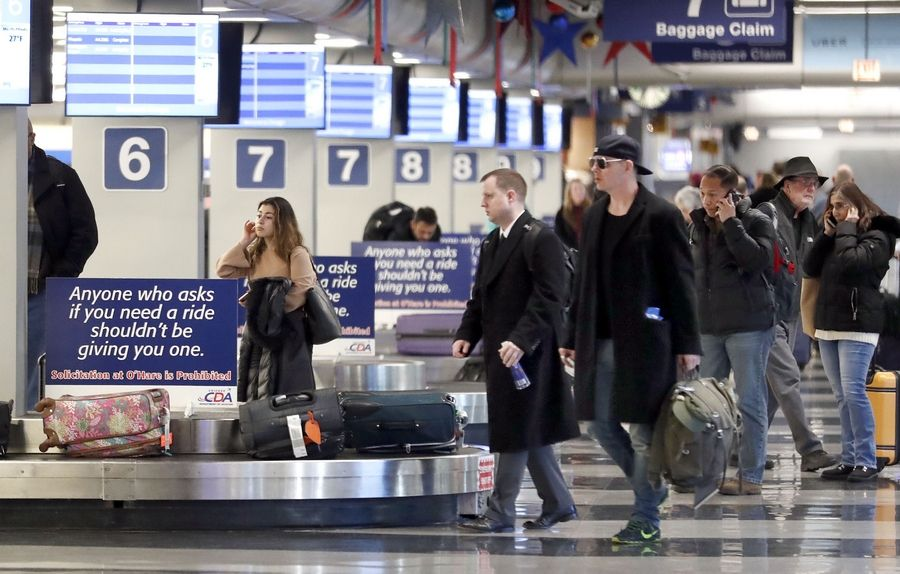 Travelers pick up their luggage from the arrivals level at O'Hare International Airport's Terminal 3. A new federal rule offers consumers more information about damaged wheelchairs and mishandled luggage.