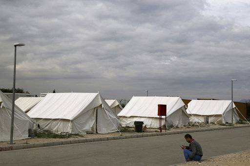 In this Tuesday, Nov. 27, 2018, a migrant from Syria rests at a refugee camp in Kokkinotrimithia outside of Nicosia, Cyprus. The Cyprus Refugee Council, a nonprofit group, said there is now a backlog of about 8,000 asylum applications as of late 2018, and it takes three to five years to process each claim, including appeals.(AP Photo/Petros Karadjias)