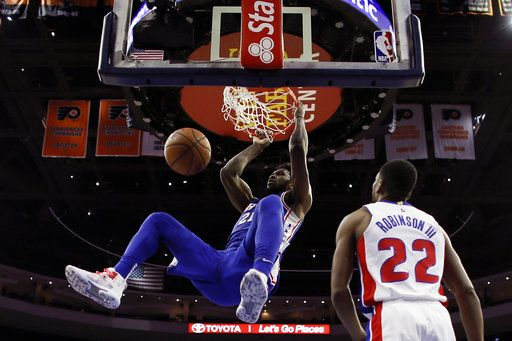 Philadelphia 76ers' Joel Embiid, left, hangs from the rim after a dunk past Detroit Pistons' Glenn Robinson III (22) during the first half of an NBA basketball game, Monday, Dec. 10, 2018, in Philadelphia.