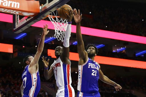 Detroit Pistons' Reggie Jackson (1) goes up to shoot between Philadelphia 76ers' Joel Embiid (21) and JJ Redick (17) during the first half of an NBA basketball game, Monday, Dec. 10, 2018, in Philadelphia.