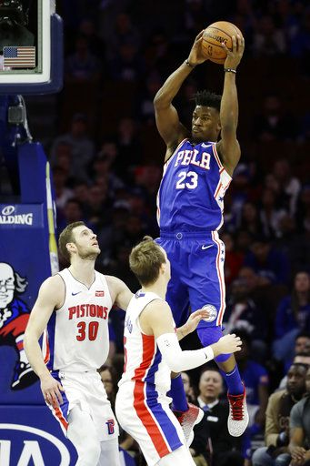 Philadelphia 76ers' Jimmy Butler (23) leaps to pass over Detroit Pistons' Luke Kennard (5) and Jon Leuer (30) during the first half of an NBA basketball game, Monday, Dec. 10, 2018, in Philadelphia.