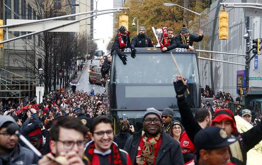 Fans cheer as a double decker bus carrying the Atlanta United FC MLS team passes during the team's victory parade in Atlanta, Monday, Dec. 10, 2018. Atlanta United defeated the Portland Timbers 2-0 in the MLS Final on Saturday night. (Bob Andres/Atlanta Journal and Constitution via AP)