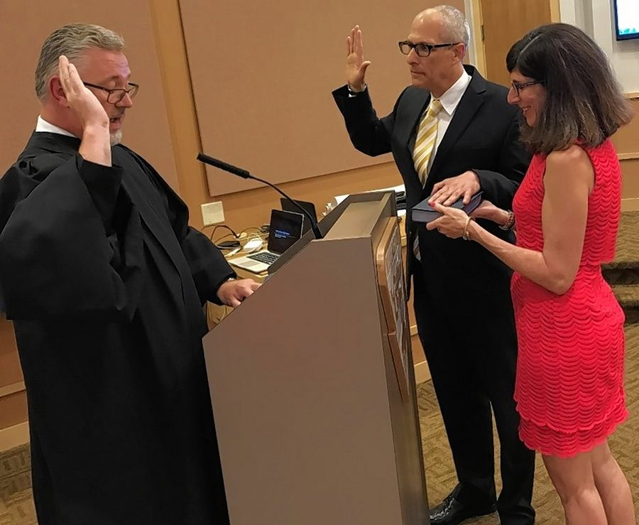 Eric Smith, standing next to his wife, Judie, was sworn in last year as a Buffalo Grove trustee by Judge and former Trustee Charles Johnson. Smith will try to hold onto his seat amid a crowded village board race next spring.