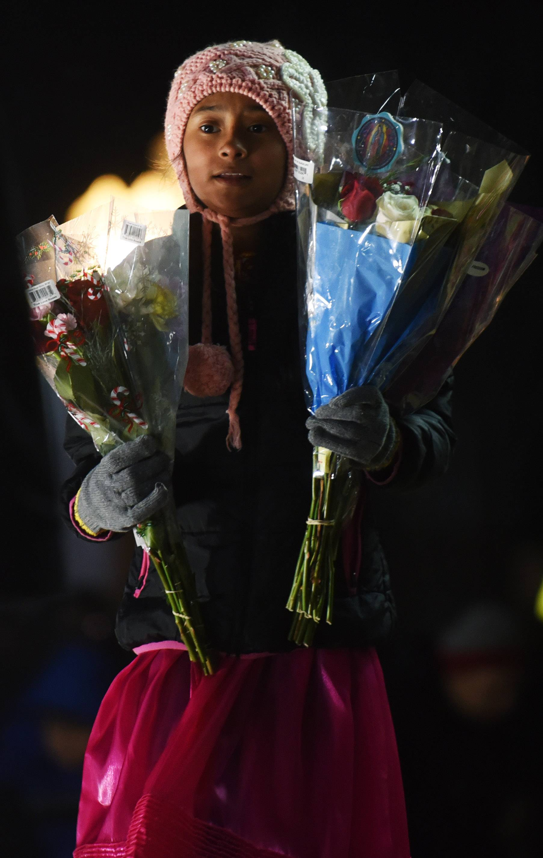Alexandra Hernandez, 12, of Carpentersville carries flowers for placement at the shrine during the Feast of Our Lady of Guadalupe in Des Plaines Tuesday.