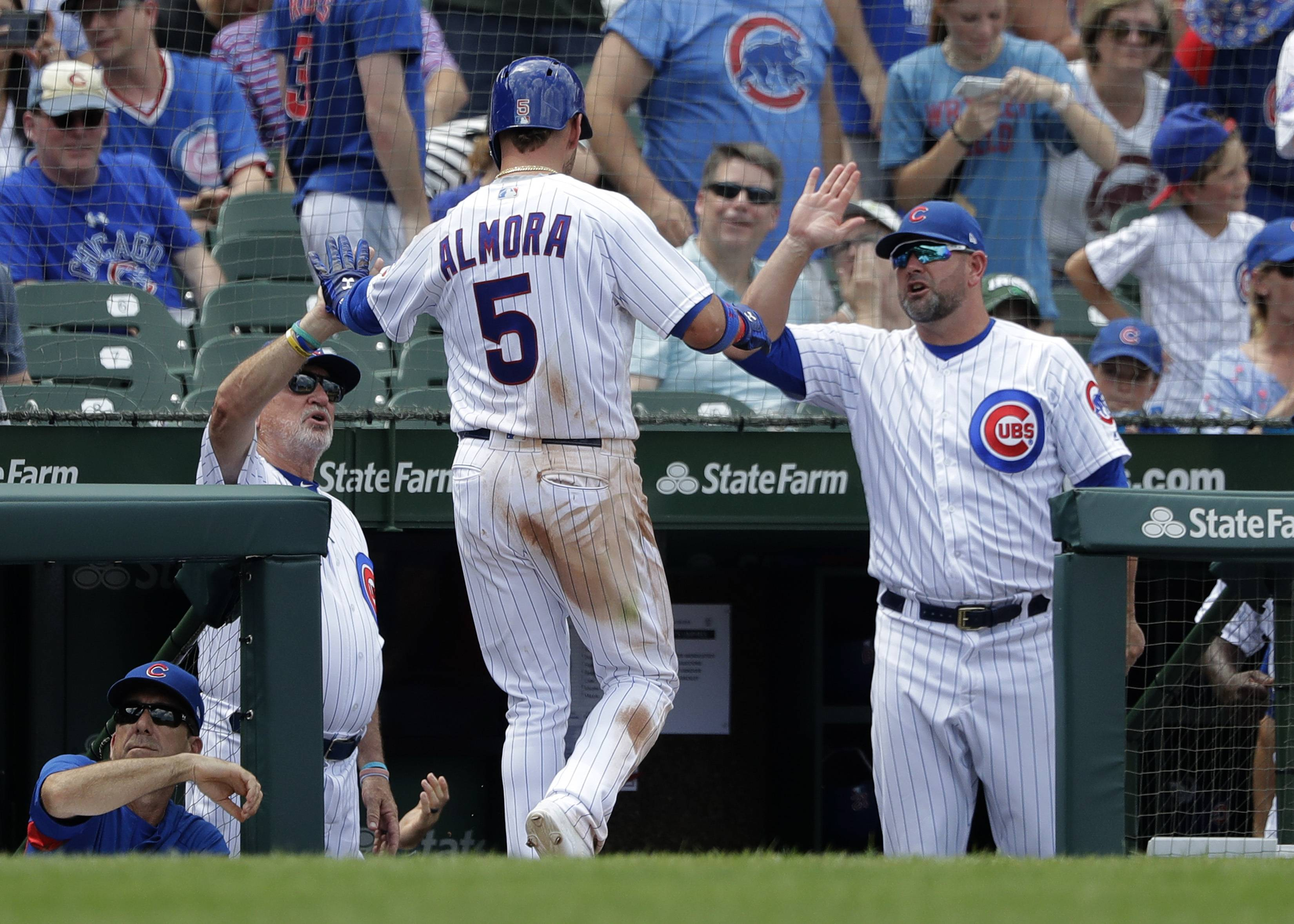 Albert Almora Jr. (5) is greeted at the dugout by manager Joe Maddon, left, and bench coach Brandon Hyde after Almora Jr., score on a single by Anthony Rizzo during a win over the Twins in June. The Baltimore Orioles denied reports Tuesday night that they had chosen Hyde as their new manager, saying the reports were premature and no decision was expected this week.