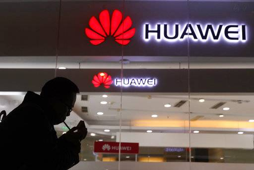 FILE - In this Thursday, Dec. 6, 2018, file photo, a man lights a cigarette outside a Huawei retail shop in Beijing. Taiwan is reinforcing its five-year-old ban on network equipment produced by Chinese companies Huawei and ZTE amid security concerns. (AP Photo/Ng Han Guan, File)
