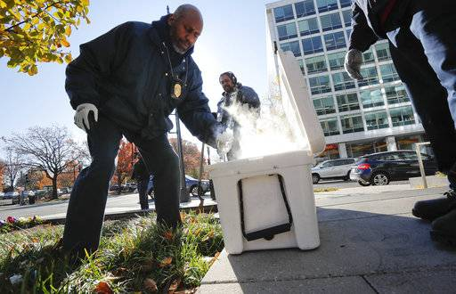 Pest Control Officers Gregory Cornes, left, uses a hand trowel to scoop-up dry ice before dropping it directly into rat burrows, as his co-worker Curtis Redman assist, near the Capitol building in Washington, Wednesday, Nov. 21, 2018. Both are from the Department of Health's Rodent Control Division. The nation's capital is facing a spiraling rat infestation, fueled by mild winters and a human population boom. Washington's government is struggling to keep pace (AP Photo/Pablo Martinez Monsivais)
