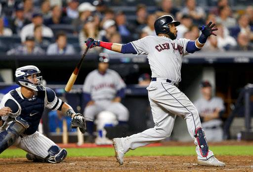 FILE - In this Oct. 9, 2017, file photo, Cleveland Indians' Carlos Santana (41) connects for a two-run home run against the New York Yankees during the fourth inning in Game 4 of baseball's American League Division Series, in New York. Edwin Encarnacion has been traded to Seattle and first baseman Carlos Santana has returned to the Indians in a three-team deal that also involved Tampa Bay. The Rays got infielder Yandy Diaz and minor league right-hander Cole Slusser from Cleveland. The Indians also acquired first baseman Jake Bauers. The swap came Thursday, Dec. 13, 2018, at the close of the winter meetings.