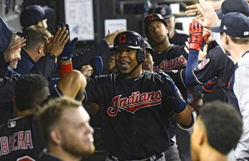 FILE - In this Sept. 26, 2018, file photo, Cleveland Indians' Edwin Encarnacion, center, celebrates in the dugout after he hit a three run home run against the Chicago White Sox during the fourth inning of a baseball game in Chicago. Encarnacion has been traded to Seattle and first baseman Carlos Santana has returned to the Indians in a three-team deal that also involved Tampa Bay. The Rays got infielder Yandy Diaz and minor league right-hander Cole Slusser from Cleveland. The Indians also acquired first baseman Jake Bauers. The swap came Thursday, Dec. 13, 2018, at the close of the winter meetings.