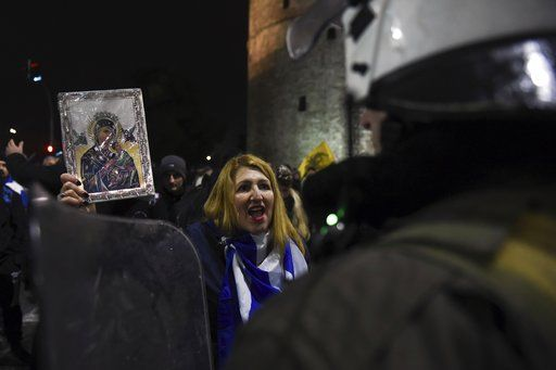 A woman holding a religious icon shouts slogans in front of riot police during a rally in the northern Greek city of Thessaloniki, Friday, Dec. 14, 2018. Hundreds of people protest against government efforts to end a three-decade-old dispute with neighboring Macedonia as the Greek Prime Minister Alexis Tsipras will deliver a speech to party cadres and supporters.