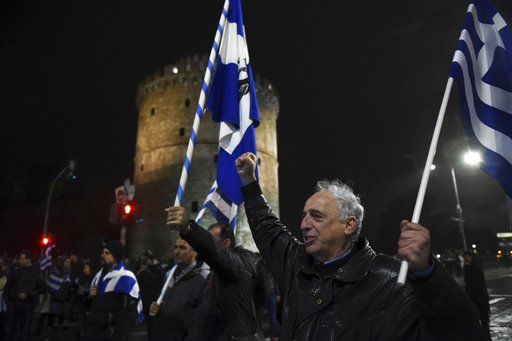 A man holding a Greek flag shouts slogans during a rally in front of the White Tower, a landmark of the northern Greek city of Thessaloniki, Friday, Dec. 14, 2018. Hundreds of people protest against government efforts to end a three-decade-old dispute with neighboring Macedonia as the Greek Prime Minister Alexis Tsipras will deliver a speech to party cadres and supporters.