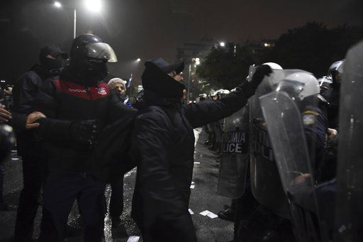 Hooded protesters gesture in front of riot police during a rally in the northern Greek city of Thessaloniki, Friday, Dec. 14, 2018. Hundreds of people protest against government efforts to end a three-decade-old dispute with neighboring Macedonia as the Greek Prime Minister Alexis Tsipras will deliver a speech to party cadres and supporters.