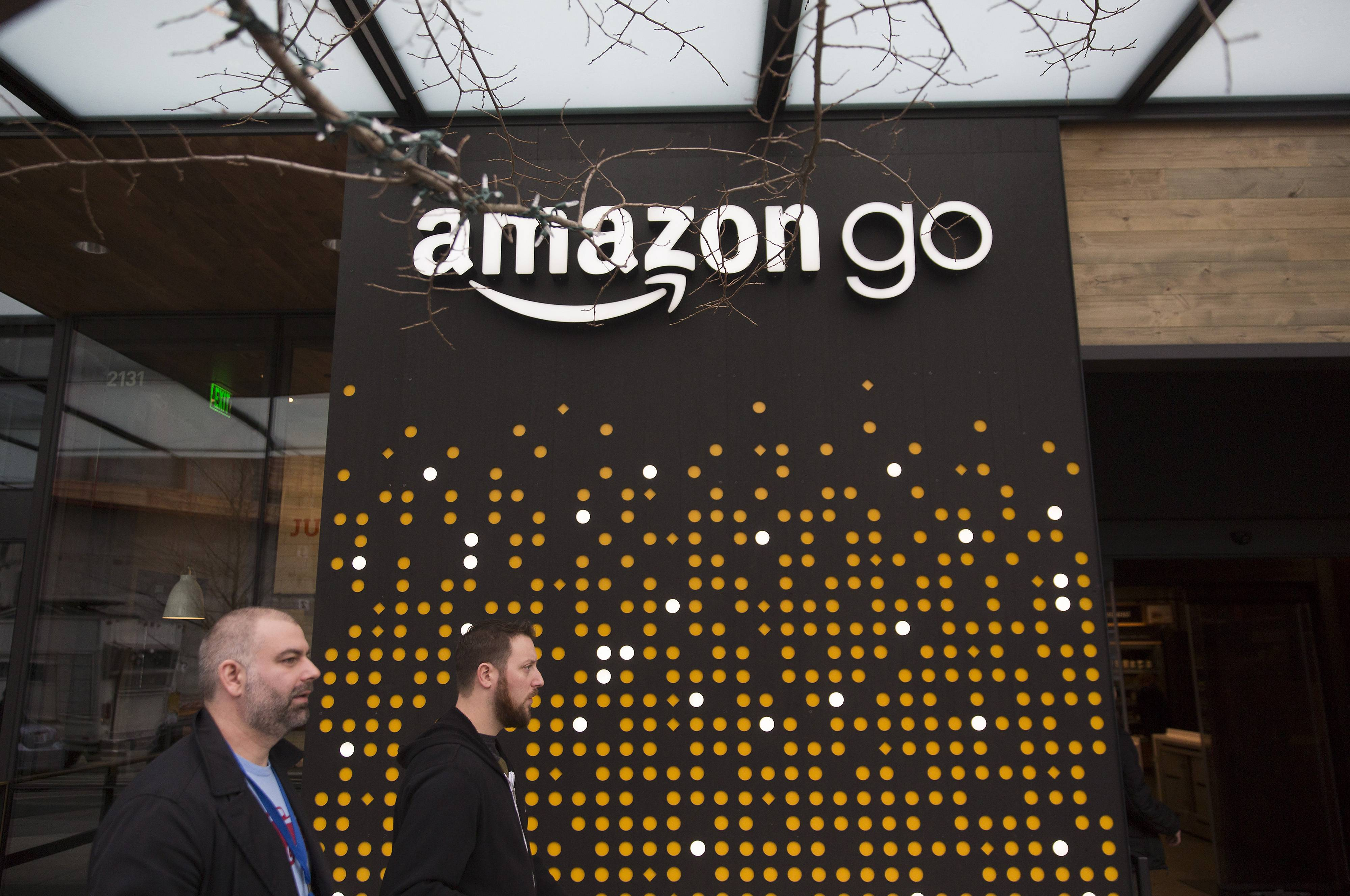 Pedestrians walk past the Amazon Go store in Seattle on Jan. 17, 2018.