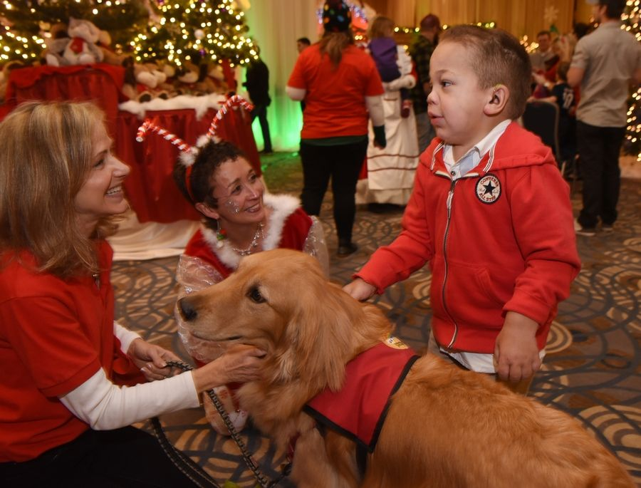"Urijah Radke, a 9-year-old from Kankakee, visits with ""Archie,"" a golden retriever from Rainbow Animal Assisted Therapy during the Operation North Pole holiday party Saturday, an annual tradition held at the Donald E. Stephens Convention Center for seriously ill children and their families. With him are Jodi Hubly, of Elk Grove Village, left, and Jamee Heelan, of Mundelein."