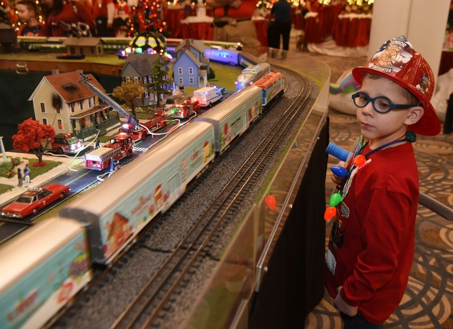 "Brody Ahern, a 6-year-old who is receiving treatment for leukemia, watches a model of the Metra train he rode earlier in the day roll past during Operation North Pole festivities. ""This event is so awesome,"" his mom Megan said. ""All of these people who devote their time to volunteer, I was not expecting this many cops and firefighters, and just all these people put it together."""