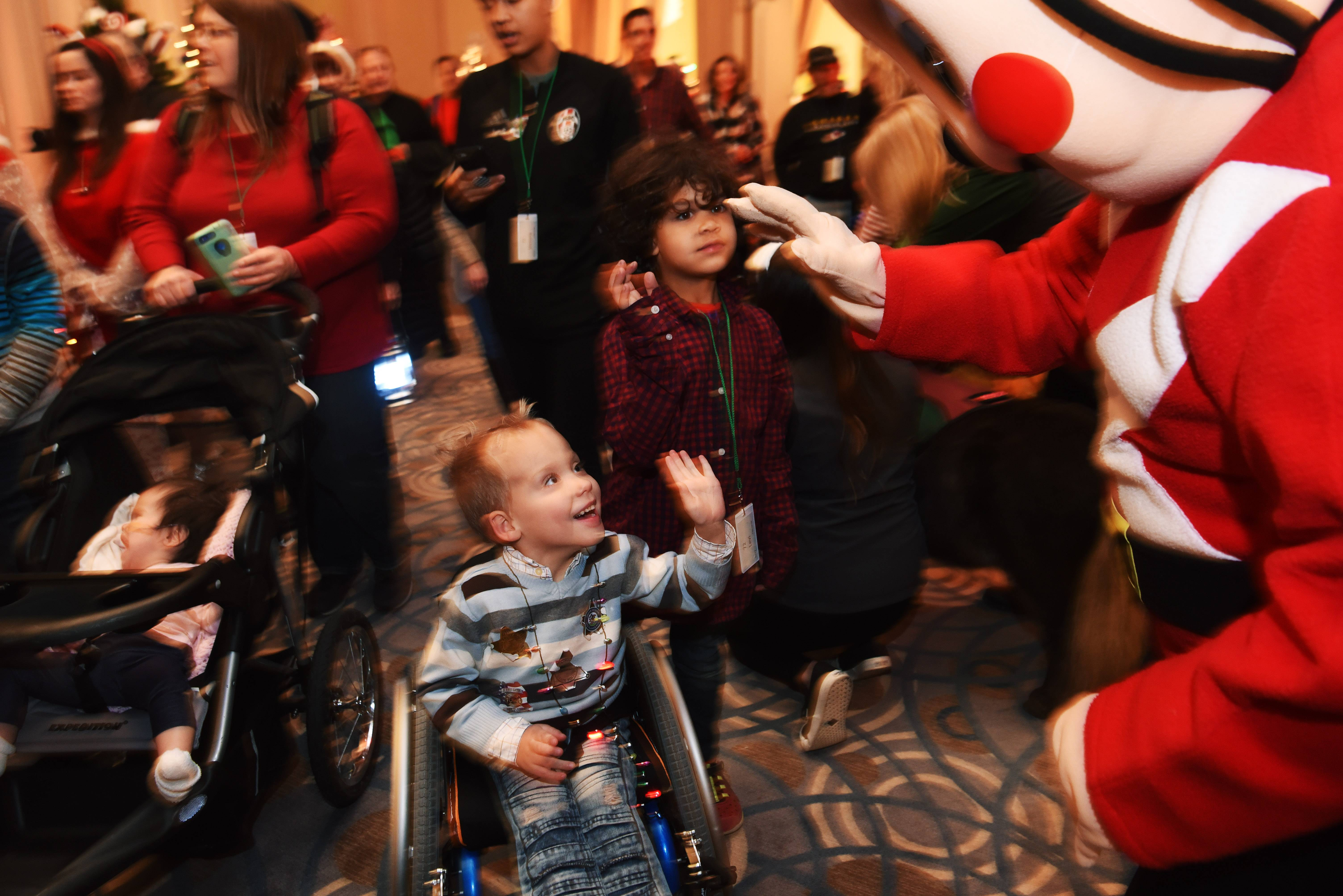 Isaac Yundt, 4, front, and his brother Levi, 6, of Poplar Grove are greeted as they make their entrance into the Operation North Pole holiday event at the Donald E. Stephens Convention Center in Rosemont Saturday.
