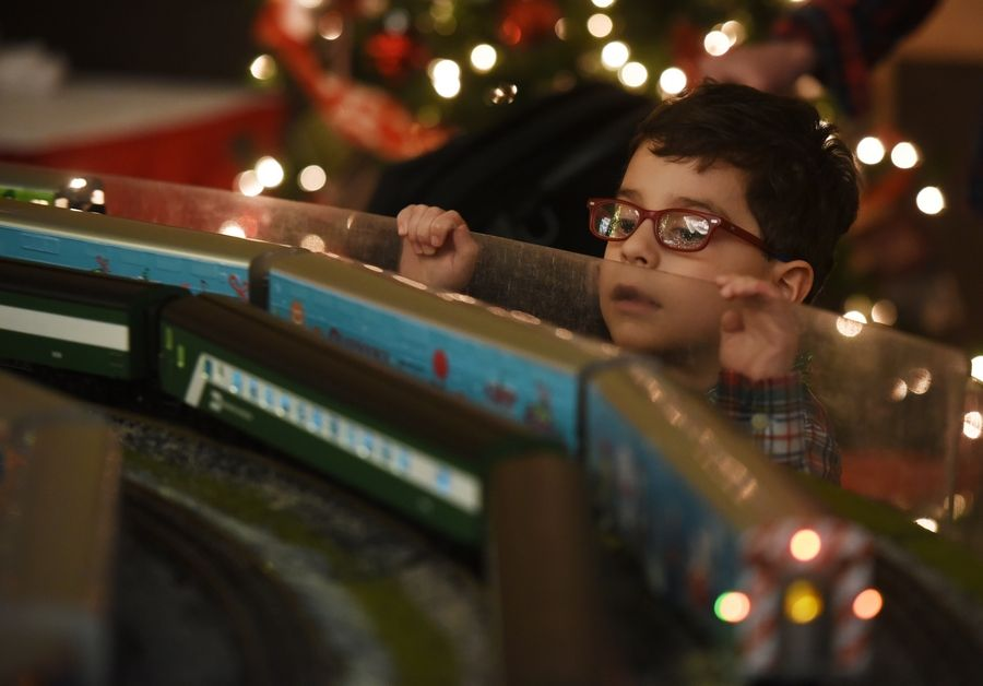 Reid Hopkins, 5, of Chicago's Edison Park neighborhood, watches model trains roll past during the Operation North Pole holiday event for seriously ill children and their families, held at the Rosemont Convention Center Saturday.