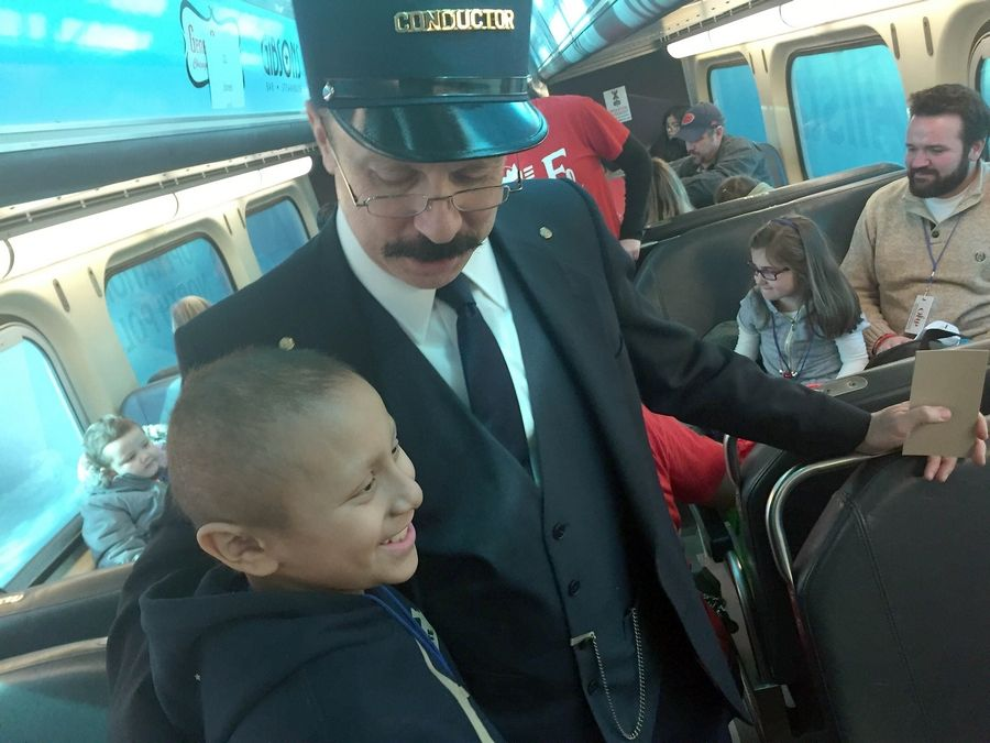 "Angel Martinez, a 9-year-old from Lake in the Hills, meets a conductor aboard a ""Polar Express"" train ride from Des Plaines to Crystal Lake and back as part of Operation North Pole."
