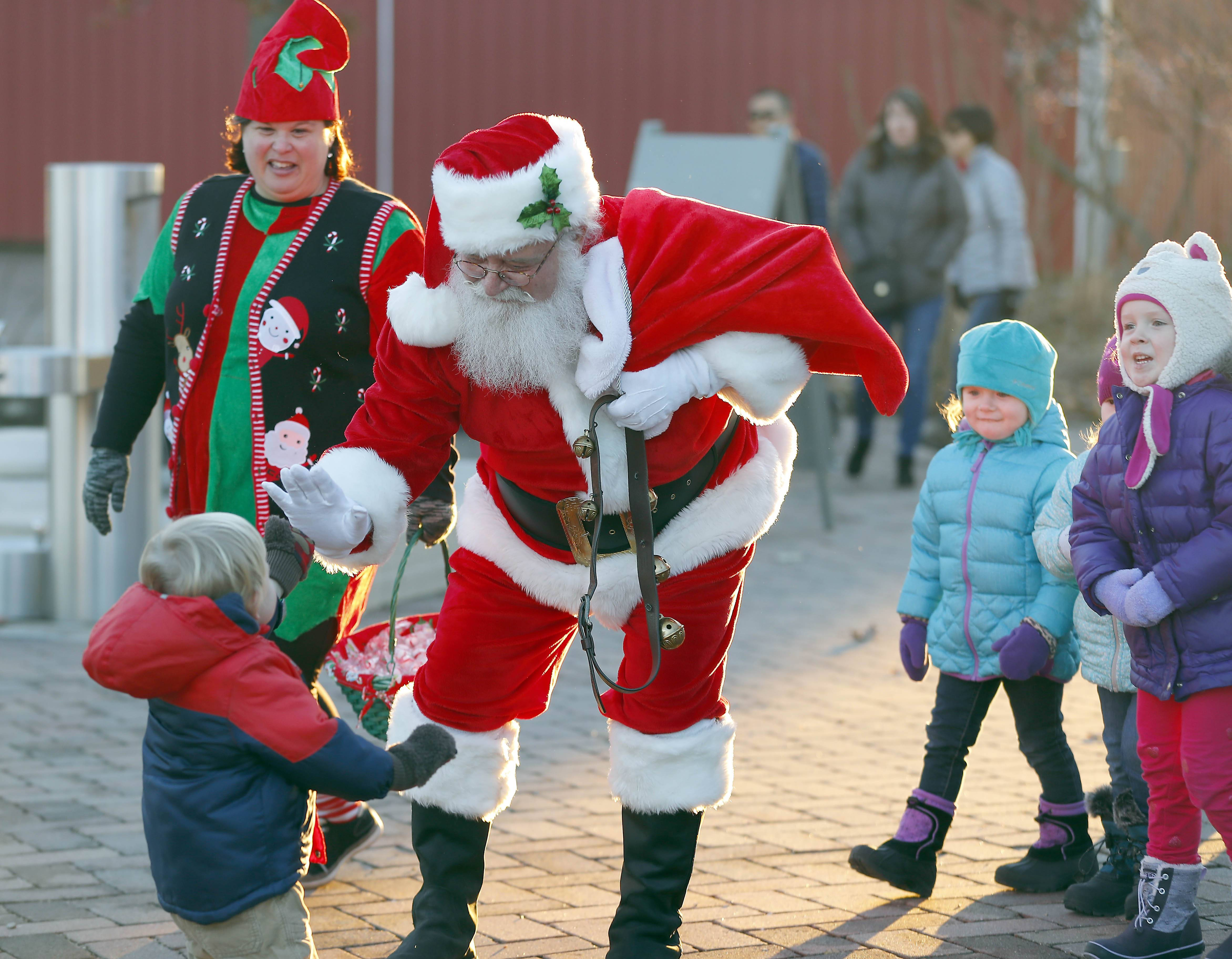 Santa gets a high-five from Kaden Oberg, 2, of Elburn, Saturday during Christmas on the Farm at Peck Farm Park in Geneva. People got to spend the evening enjoying some of the pleasures of Christmas past.