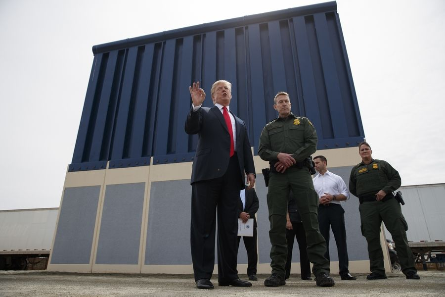 President Donald Trump stands in front of a border wall prototype in San Diego in March.