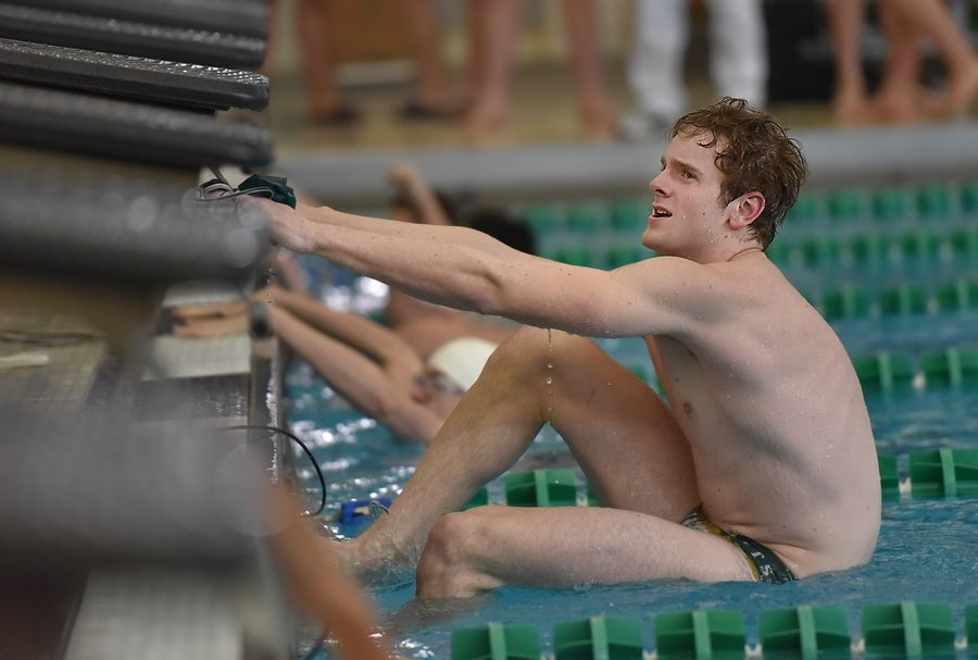Topher Stensby, of Stevenson High School, climbs out to the pool after winning the 50-yard freestyle at the Lake County boys swimming meet at Stevenson High School in Lincolnshire Saturday.