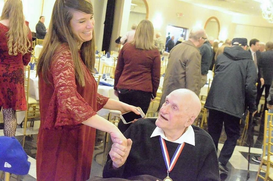 Everett Schlegel of Elgin, a Pearl Harbor attack survivor, is greeted by Melissa Schulenburg of Geneva at the annual Pearl Harbor Day luncheon Dec. 10 at Gaslite Manor Banquets in Aurora. Schulenburg's daughter, Christina, was among 10 youth honored with service awards.