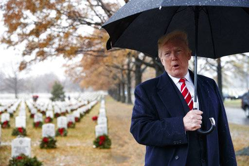 President Donald Trump speaks to media he visits Section 60 at Arlington National Cemetery in Arlington, Va., Saturday, Dec. 15, 2018, during Wreaths Across America Day. Wreaths Across America was started in 1992 at Arlington National Cemetery by Maine businessman Morrill Worcester and has expanded to hundreds of veterans' cemeteries and other locations in all 50 states and beyond. (AP Photo/Carolyn Kaster)